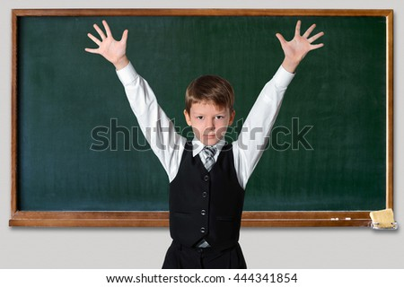 Schoolboy  in front of a green chalkboard  with hands up, Education and school concept - stock photo