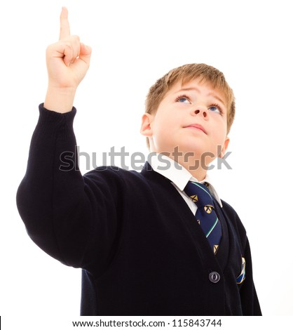 Schoolboy in his uniform points upwards. Isolated on white. - stock photo