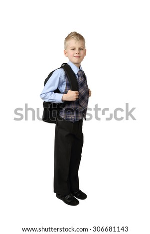 Schoolboy in uniform with school backpack on back stays isolated on white background