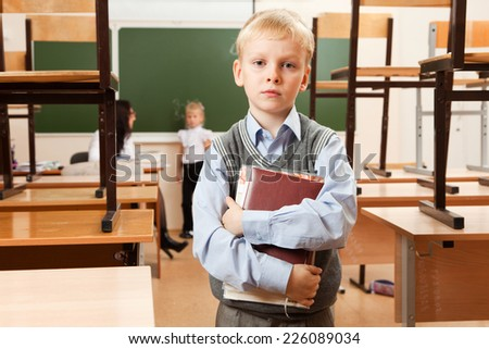 Schoolboy is in the half empty classroom after classes. He holds copybooks in his hands. He is bored. Teacher is teaching schoolgirl behind him.