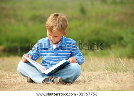 schoolboy is  reading  a big  book on the background of green meadows