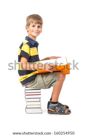 Schoolboy is sitting on books isolated on a white background. Back to school