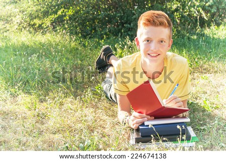 Schoolboy left-handed teen (teenager) lying and writing in the park. Young smiling red-head boy studying on the grass. Caucasian cute male model (14 year). Sunny day. Education concept. Copy space. - stock photo