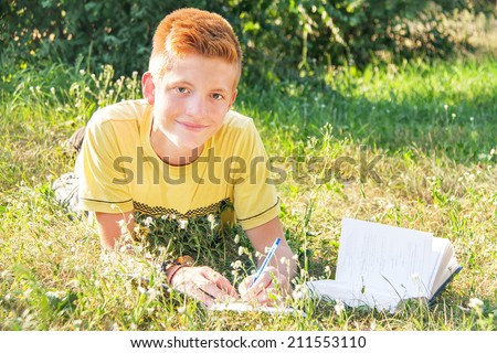 Schoolboy left-handed teen (teenager) lying, writing and reading in the city park. Young smiling red-head boy studying on the grass. Caucasian cute male model. Sunny day. Education concept. Close up.  - stock photo