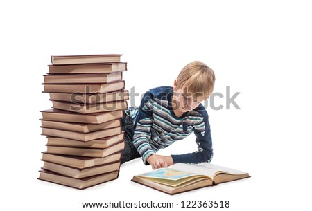 Schoolboy lying and looking at the maps in the book, on white background