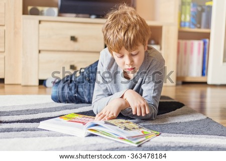 Schoolboy lying down and reading a book - stock photo