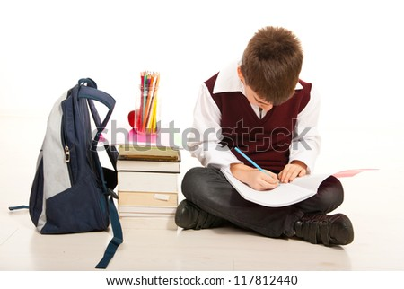 Schoolboy making homework and sitting with legs crossed on the floor isolated on white background - stock photo