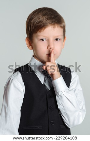 Schoolboy making sign with his finger to keep silence - stock photo