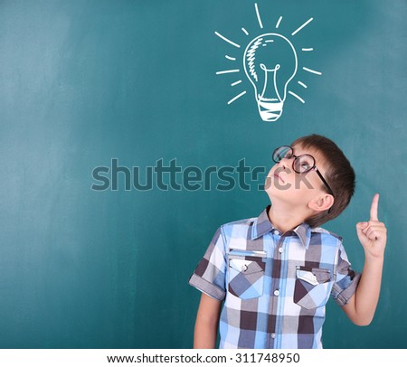 Schoolboy near blackboard with idea bulb above the head - stock photo