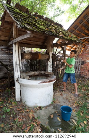 Schoolboy outdoor getting water from a vintage wooden well with pulley - stock photo