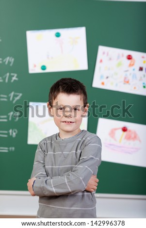 Schoolboy posing with arms crossed in front of blackboard - stock photo