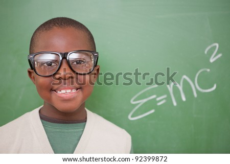 Schoolboy posing with the the mass-energy equivalence formula on a blackboard - stock photo