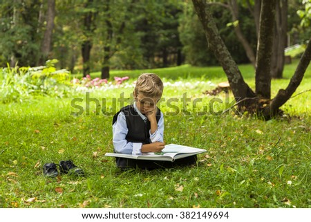 schoolboy reading book in the park, child studying outdoors - stock photo