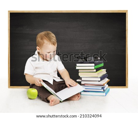 Schoolboy reading book near blackboard, kindergarten school boy, little child on black board background, elementary education concept - stock photo
