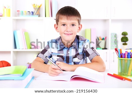 Schoolboy sitting at table in classroom - stock photo