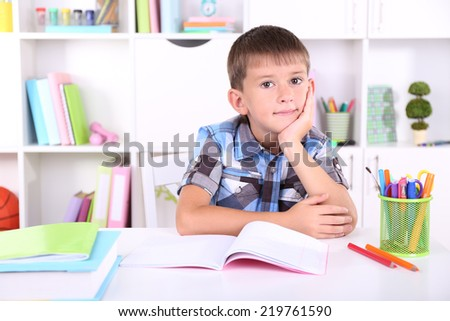 Schoolboy sitting at table in classroom