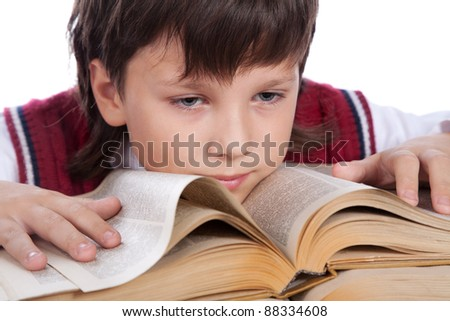schoolboy sitting at the table with big book - stock photo