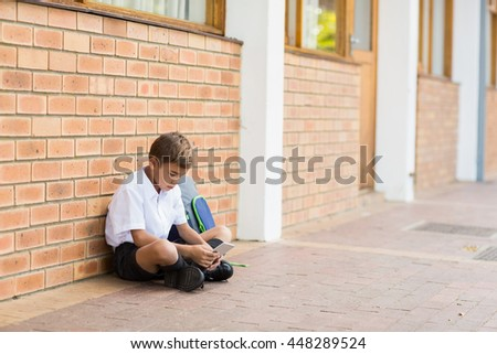 Schoolboy sitting in corridor and using mobile phone at school - stock photo