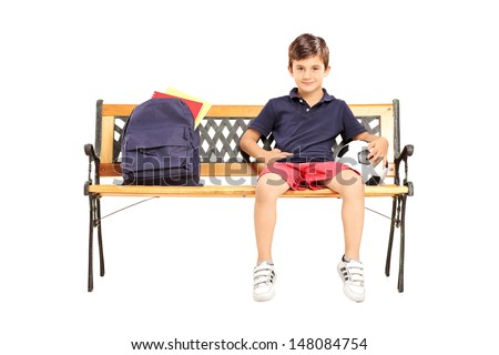 Schoolboy sitting on a wooden bench with school bag and football isolated on white background - stock photo