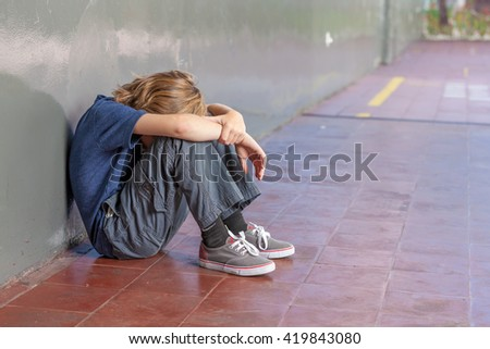 Schoolboy sitting on floor at school. Bullying and isolation concept. - stock photo