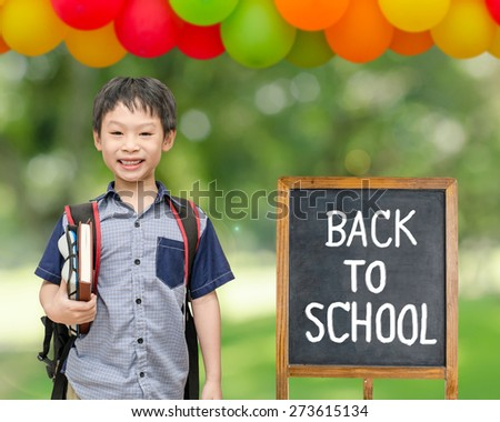 Schoolboy smiles with chalkboard at school - stock photo
