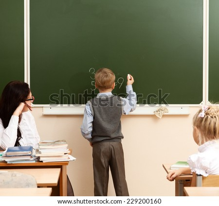 Schoolboy solves example at the school board during a lesson in mathematics. - stock photo