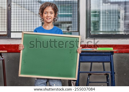 Schoolboy standing holding empty chalkboard. - stock photo