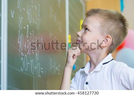 Schoolboy standing near blackboard with formula - stock photo