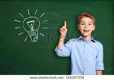 Schoolboy standing near blackboard with light bulb - stock photo