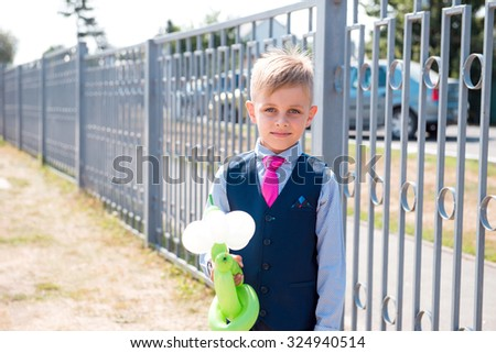 Schoolboy standing near fence dressed in costume with balloons - stock photo