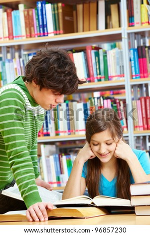 Schoolboy standing near his friend in library while she reading book with a smile