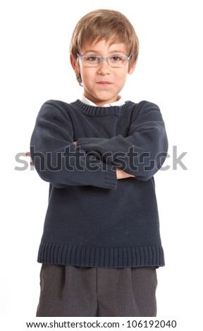 Schoolboy standing with his arms crossed - stock photo