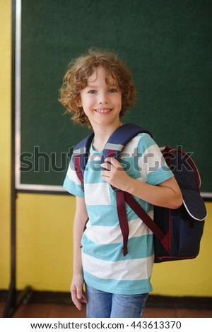 Schoolboy stands in the class near a board. Behind shoulders at it a school backpack. The school student looks in the camera and smiles. Back to school.