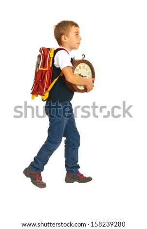 Schoolboy walking to school and holding clock isolated on white background