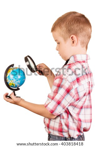 Schoolboy with a magnifying glass carefully examines the globe isolated on white background. - stock photo