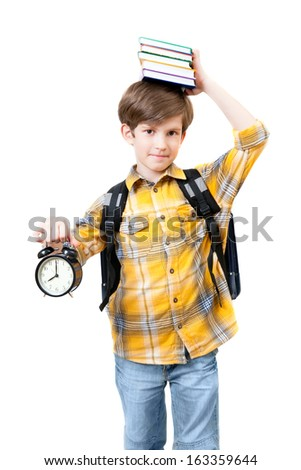 schoolboy with alarm clock keeps on the head stack of books - stock photo
