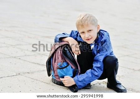 schoolboy with backpack sitting and smiling - stock photo