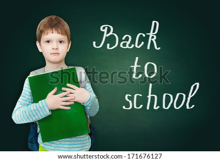"Schoolboy with bag and books on a green blackboard with the words ""back to school""."