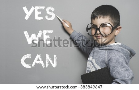 schoolboy with goggles and funny gesture writing on the blackboard the text yes we can