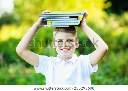 Schoolboy with huge stack of books - stock photo