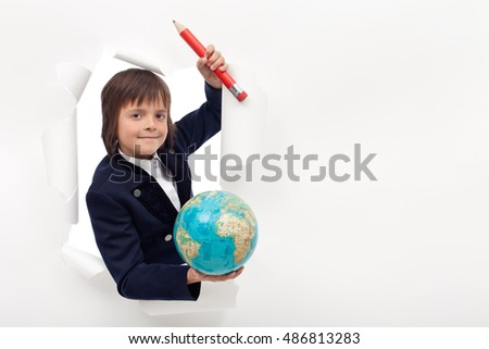 Schoolboy with large pencil and earth globe - with large copy space on white paper layer