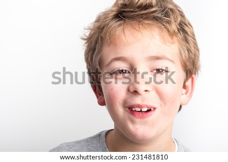 Schoolboy with long hair making faces - stock photo