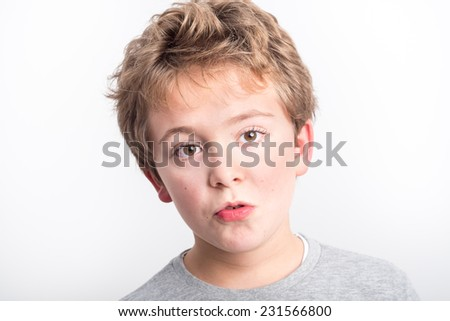 Schoolboy with long hair making funny faces - stock photo