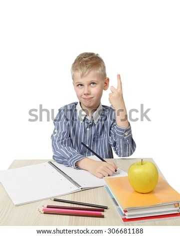 Schoolboy with raised forefinger sits near the desk with school supplies and big apple on foreground isolated on white background - brilliant idea came - learning and homework - stock photo