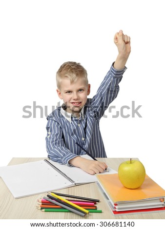 Schoolboy with raised hand sits near the desk with school supplies and big apple on foreground isolated on white background - ready to answer - learning and homework - stock photo
