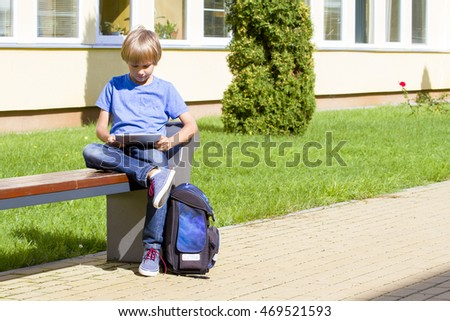 Schoolboy with tablet PC sitting on the bench near school. Outdoor. Education, technology, people concept