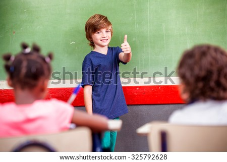 Schoolboy with thumb up during a lesson. - stock photo