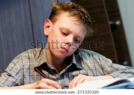 Schoolboy with wet hair makes school homework at the table - stock photo