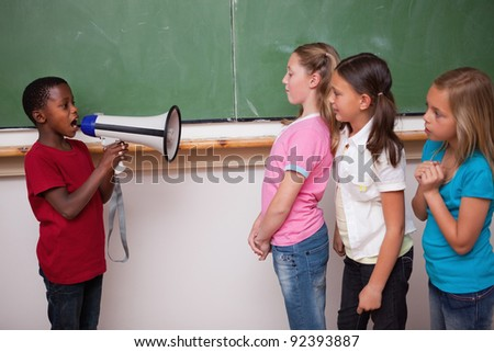 Schoolboy yelling through a megaphone to his classmates in a classroom