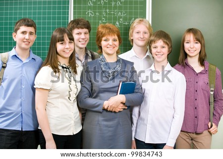 Schoolboys and schoolgirls with teacher in classroom